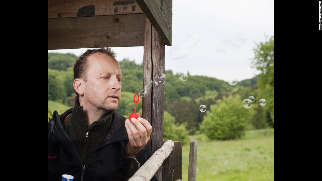 Jens Stormer, a hunter, blows soap bubbles to see which way the wind is going. This way, animals can't detect him.