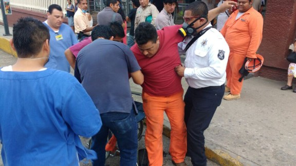 A worker receives help while being admitted to the hospital in Coatzacoalcos.