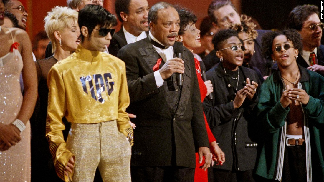 "As dozens of singers perform ""We Are The World"" on the 10th anniversary of the African famine relief anthem, the artist formerly known as Prince stands sucking on a lollipop next to Quincy Jones at the American Music Awards in Los Angeles in 1995."
