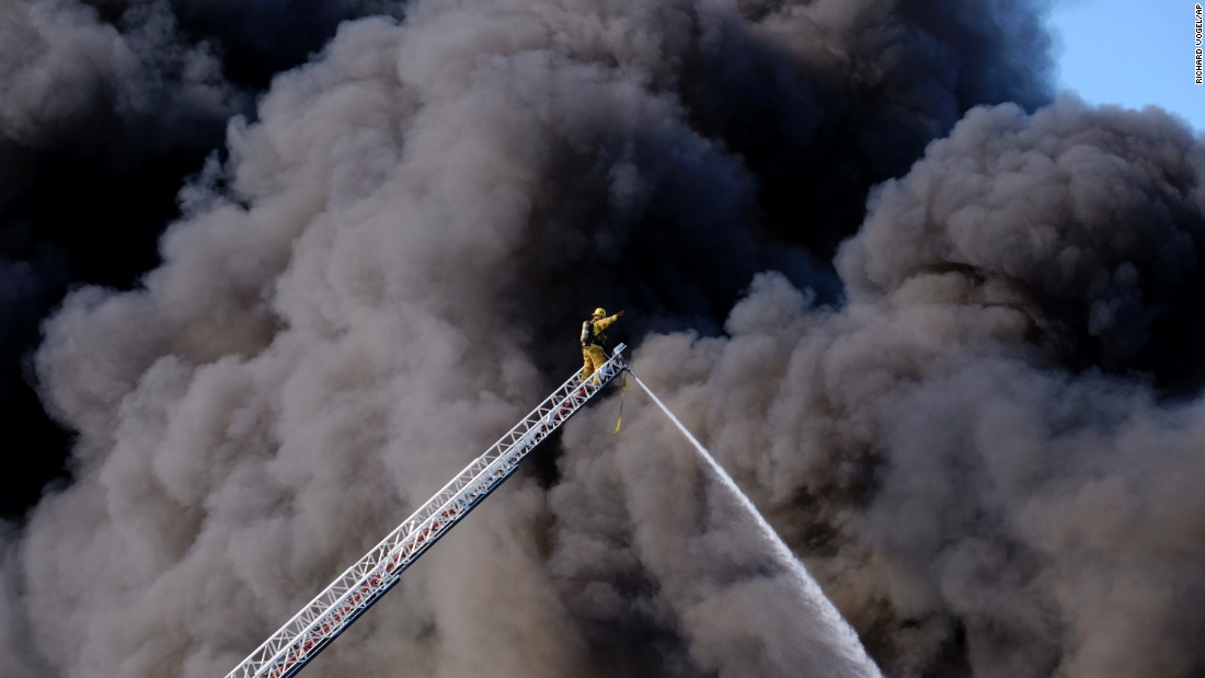 A firefighter responds to a fire at an auto wrecking yard in the Sun Valley section of Los Angeles in the San Fernando Valley as a huge plume of thick, black smoke rises over them on Sunday, April 17.