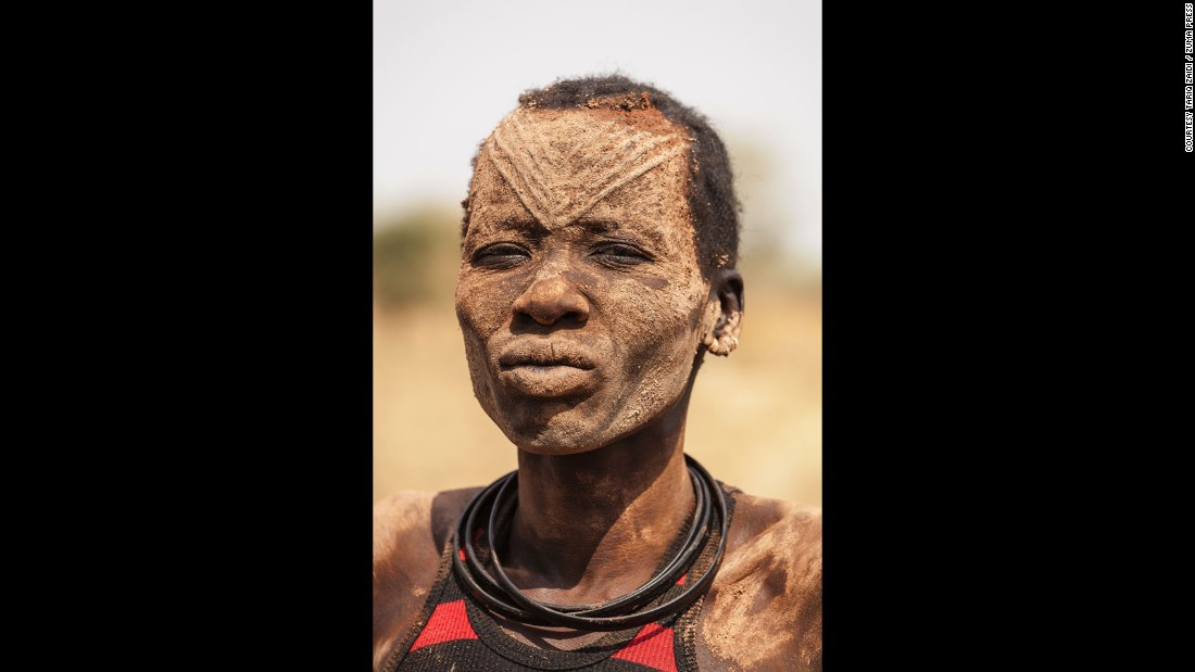 A Mundari woman with the ritual facial scarring, typical of the Mundari tribe, and covered in ash, a purported natural antiseptic which also protects the skin from insects.