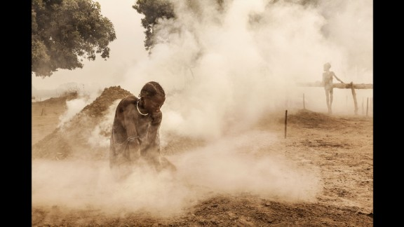 A Mundari woman clears the ground of sticks and dung before the cattle return home from the pastures. Women also milk the animals and look after the children.