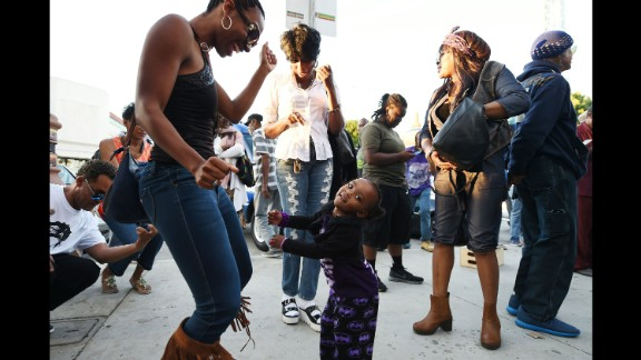 People dance in the street to the music of Prince at Leimert Park in Los Angeles on April 21.