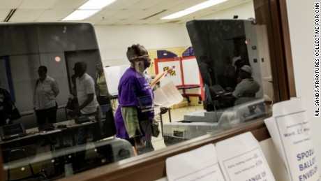 A voter submits her ballot at a polling station in West Baltimore. People are hoping the election of a new mayor will inject life in a city desperate for strong leadership. Yet some are worried that the front-runners won't bring a fresh vision.