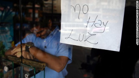 "An employee of a business closed during a blackout stands behind the door with a notice reading ""There's No Light"", in Caracas on September 3, 2013. Major power blackouts paralyzed Venezuela's capital and several states across the country on Tuesday but there was no official explanation for the cause.  AFP PHOTO/Juan Barreto        (Photo credit should read JUAN BARRETO/AFP/Getty Images)"