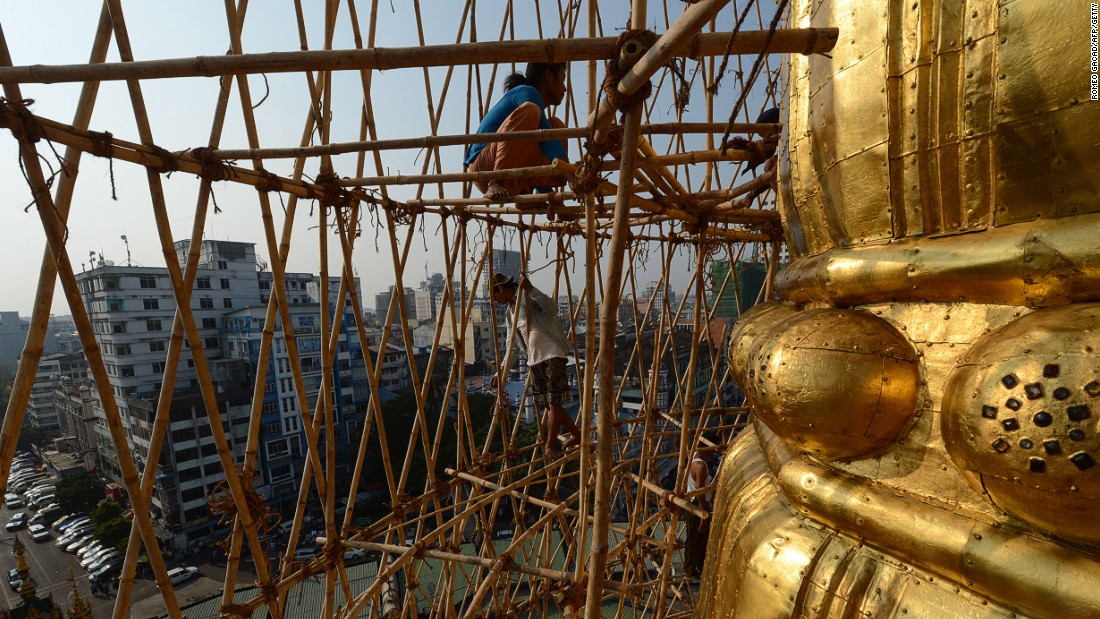 Myanmar craftsmen dismantle bamboo scaffolding on a section of the Sule Pagoda tower after installing gold covering and decorating it with gemstones.