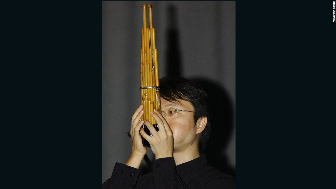 "A Japanese musician plays a traditional Japanese musical instrument called ""Sho"", which is made up of 17 slender bamboo pipes with reeds gathered together in one bundle. It makes a sound similar to an organ."
