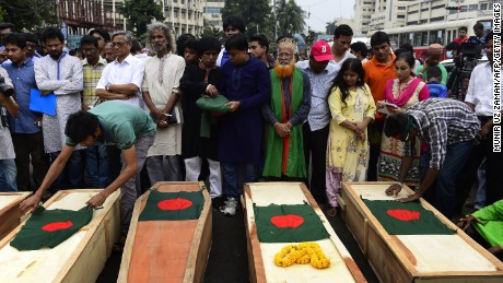 Bangladeshi activists place national flags on mock coffins, that symbolize the deaths of secular publishers and bloggers, in Dhaka on November 5, 2015. Secular activists marched with mock coffins to protest the recent murder of a publisher and attempted murder of writers and bloggers that have been claimed by Islamic extremists. AFP PHOTO/ Munir uz ZAMAN        (Photo credit should read MUNIR UZ ZAMAN/AFP/Getty Images)