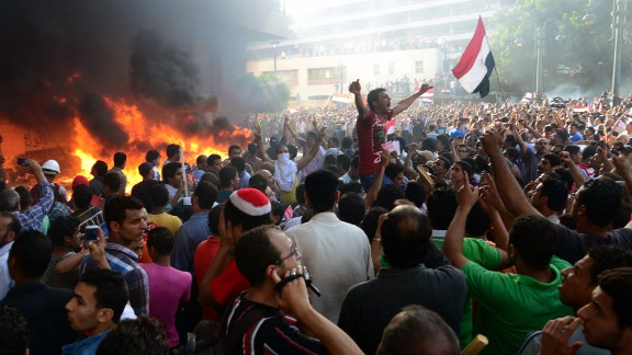 Morsy opponents chant slogans as fire rages at the Muslim Brotherhood headquarters in Alexandria in June 2013. Months earlier, Morsy granted himself unprecedented executive powers, preventing any court from overturning his decisions. He refused to bow to an ultimatum, issued by Egypt's military leaders, to find a solution to violence in the country or leave his post.