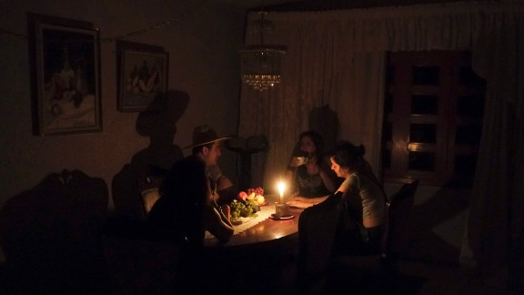 A family sit at a candle lit table in the state of Barinas, Venezuela on April 25.