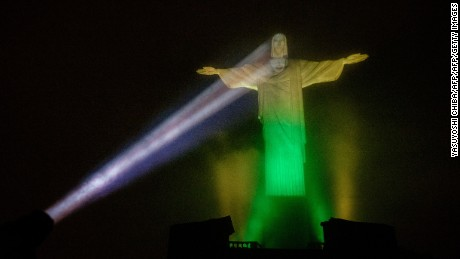 The statue of Christ the Redeemer is illuminated in Brazilian flag colors, including a projected face designed by Brazil based Italian-French lighting artist Gaspare Di Caro, to celebrate 100 days until the start of the Olympic Games Rio 2016, in Rio de Janeiro on April 27, 2016. Rio de Janeiro on Wednesday launched the 100 day countdown to hosting South America's first Olympic Games with government and global sports leaders insisting they can overcome Brazil's political meltdown and troubled preparations. / AFP / YASUYOSHI CHIBA        (Photo credit should read YASUYOSHI CHIBA/AFP/Getty Images)