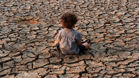 A child sits at an area affected by a drought on Earth Day in the southern outskirts of Tegucigalpa, Honduras.