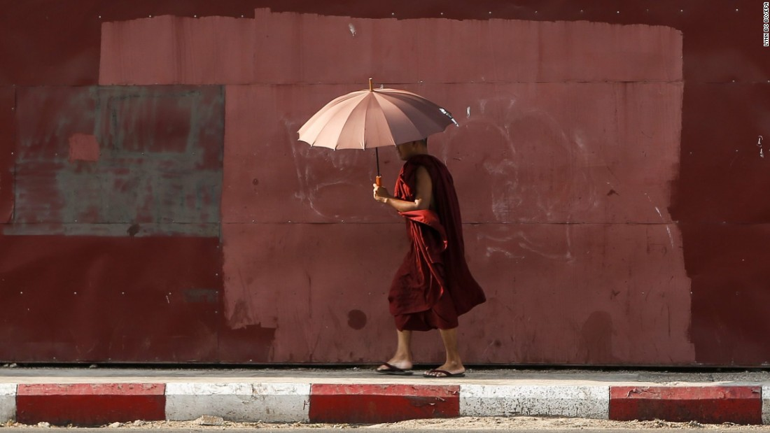 A Buddhist monk uses an umbrella to protect himself from the sun in Yangon, Myanmar, on Tuesday, April 26.