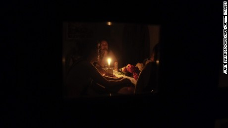 A family sit at a candle lit table in their darkened residence in the state of Barinas, 600 km west of Caracas on April 25, 2016. Recession-hit Venezuela will turn off the electricity supply in its 10 most populous states for four hours a day for 40 days to deal with a severe power shortage, the government said. It is the latest drastic measure by the government in a crisis that already has Venezuelans queuing for hours to buy scarce supplies in shops. / AFP / JUAN BARRETO        (Photo credit should read JUAN BARRETO/AFP/Getty Images)