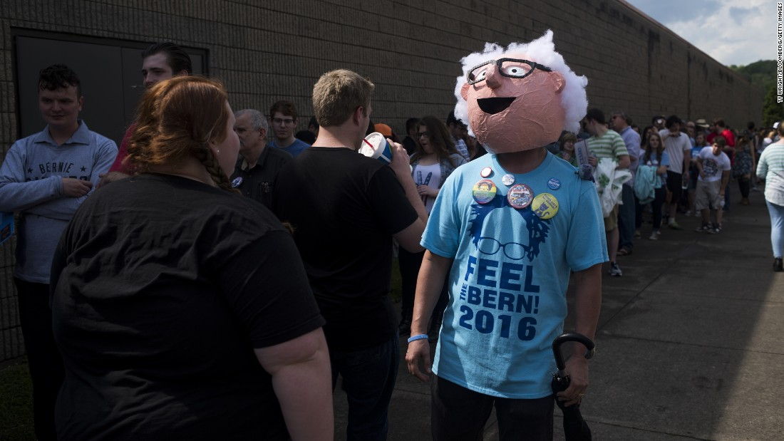 A man wears a mask of U.S. Sen. Bernie Sanders while waiting in line for a campaign event in Huntington, West Virginia, on Tuesday, April 26.