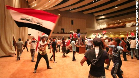 "Iraqi protesters wave national flags inside Parliament after breaking into Baghdad's heavily fortified ""Green Zone"" on April 30, 2016."