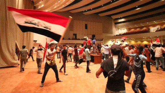 """Iraqi protesters wave national flags inside Parliament after breaking into Baghdad's heavily fortified """"Green Zone"""" on April 30, 2016."""