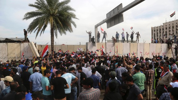 Supporters of Shiite cleric Muqtada al-Sadr walk over the blast walls surrounding Baghdad's highly fortified Green Zone Saturday, April 30, 2016.