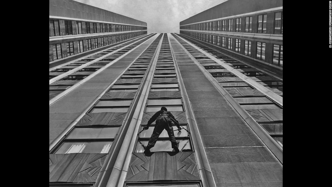 A window cleaner hangs suspended from the exterior of The Empire State Building while using a leather safety harness in 1935.