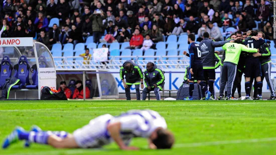 Real Madrid's players celebrate Bale's goal in the background while a Real Sociedad player feels the anguish face down.