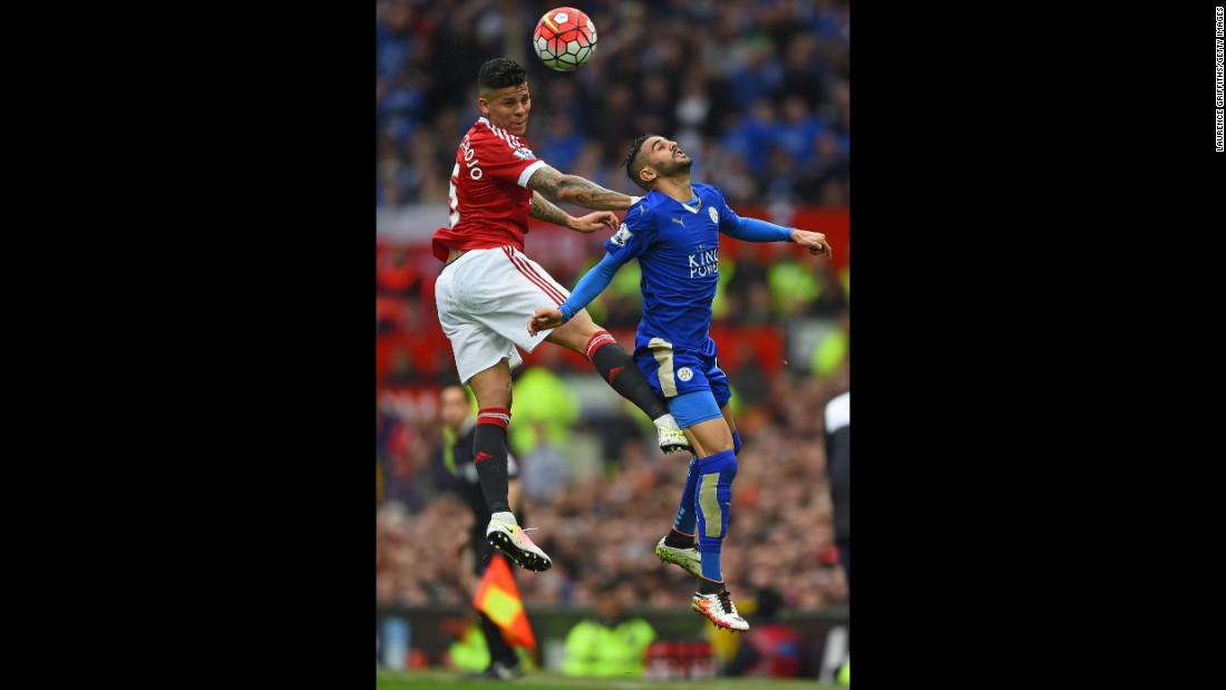 United's Argentine international Marcos Rojo wins a header with Leicester's Riyad Mahrez.