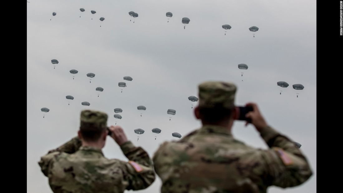 U.S. soldiers watch paratroopers take part in a training jump near Grafenwoehr, Germany, on Tuesday, April 12. The paratroopers were American, British and Italian.