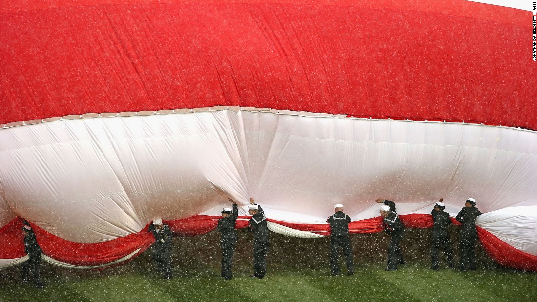 Sailors try to corral a large American flag before the home opener of the Chicago White Sox on Friday, April 8.
