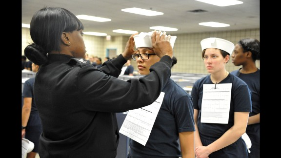 """Engineman 2nd Class Shanice Floyd, a recruit division commander, ensures the proper fit of Megan Marte's hat during uniform issue Monday, April 4, in Great Lakes, Illinois. Marte was among the first female recruits to be issued the """"Dixie cup"""" hat as part of the Navy's efforts at gender equality."""