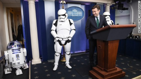 White House Press Secretary Josh Earnest speaks to the press in the briefing room at the White House in Washington, DC, on December 18, 2015 with Star Wars characters R2D2 and Storm Troopers.