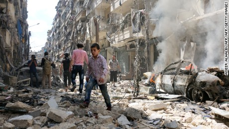 TOPSHOT - People walk amid the rubble of destroyed buildings following a reported air strike on the rebel-held neighbourhood of al-Kalasa in the northern Syrian city of Aleppo, on April 28, 2016. The death toll from an upsurge of fighting in Syria's second city Aleppo rose despite a plea by the UN envoy for the warring sides to respect a February ceasefire. / AFP / AMEER ALHALBI        (Photo credit should read AMEER ALHALBI/AFP/Getty Images)