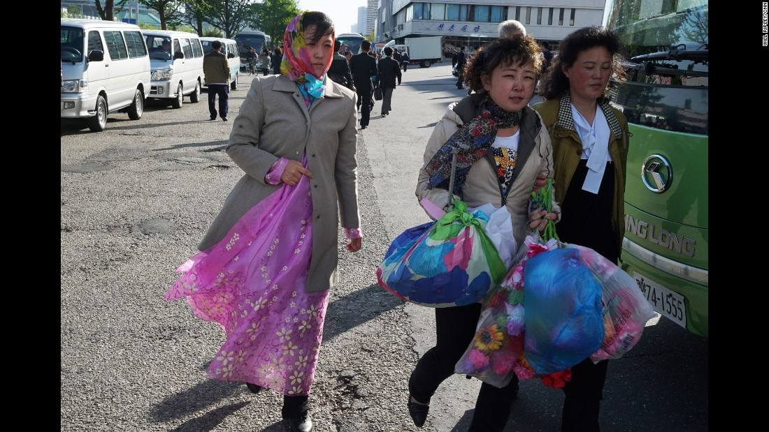 Everywhere you look people are carrying home bags of artificial flowers. They are standard issue for all major celebrations in North Korea.