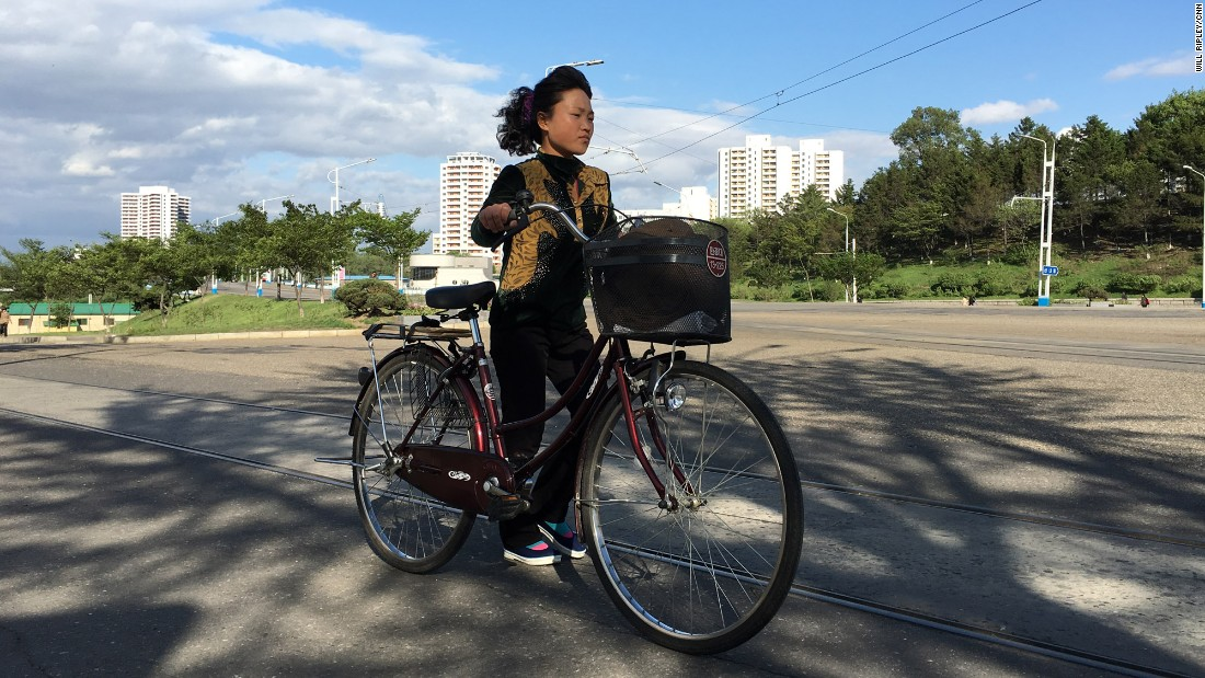 "A woman walks her bike along Kwangbok ""Liberation"" street in Pyongyang on May 4 after a day of work and rehearsals for the upcoming congress."