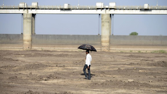 A man walks on the dry reservoir bed next to Gunda Dam in India