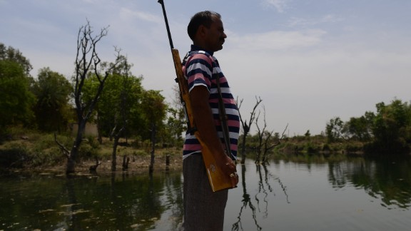 A gunman stands guard at a water reservoir in the central Indian state of Madhya Pradesh on Wednesday, April 27, 2016.
