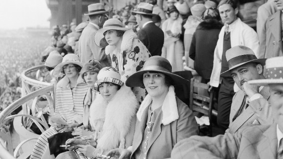 """The Derby first launched in 1875, and up until the turn of the 20th century women could be seen wearing hats, gloves, and long dresses down to their ankles. """"At any social outing in America at that time, you would have worn a hat and gloves -- and the Kentucky Derby was no different,"""" said Chris Goodlet, Curator of Collections at the Kentucky Derby Museum. """"Many women would have worn silk because of the warm weather, and be carrying a parasol."""" This image features race-goers in 1926."""