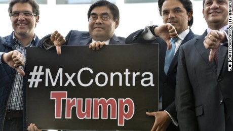 Mexican Senators of left-wing Party of the Democratic Revolution (PRD) hold a sign with a hashtag against US Republican presidential candidate Donald Trump as they give their thumbs down in Mexico City on March 29, 2016.     AFP PHOTO/ Yuri CORTEZ / AFP / YURI CORTEZ        (Photo credit should read YURI CORTEZ/AFP/Getty Images)