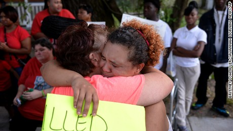 Martha Holmes, left, hugs Janie Smith, older sister of Charles Smith, who was shot and killed on Augusta Avenue by police in 2014.