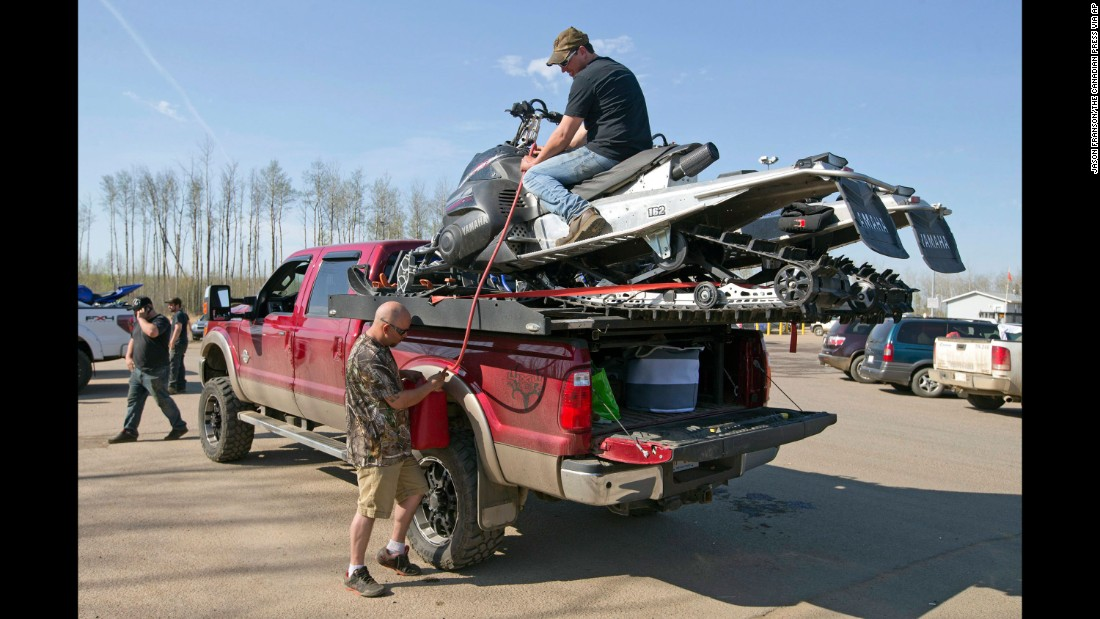 Robert Parker, left, and Matt Jones siphon gas from two snowmobiles for their truck on May 4.