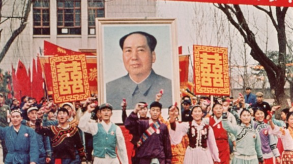 Supporters march down the street carrying a large poster of Chairman Mao Zedong.
