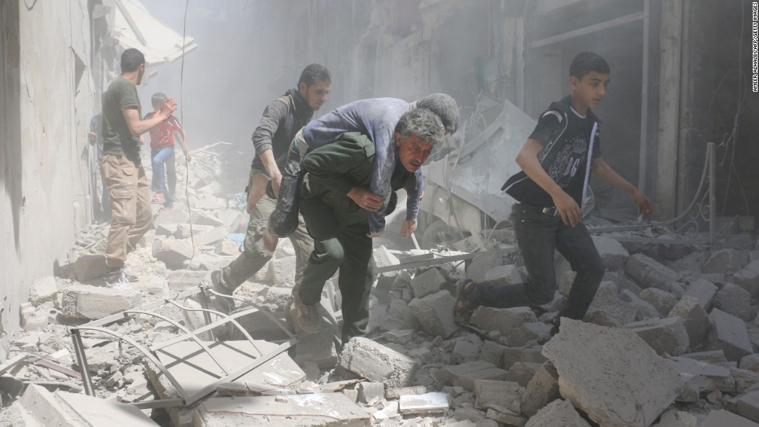An injured man is carried away from the scene of a reported airstrike in Aleppo, Syria, on Friday, April 29. The city has been battered by the country's civil war.
