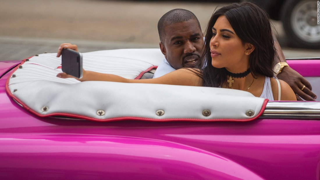 Television personality Kim Kardashian takes a selfie next to her husband, rapper Kanye West, as they ride in the back seat of a car in Havana, Cuba, on Wednesday, May 4.