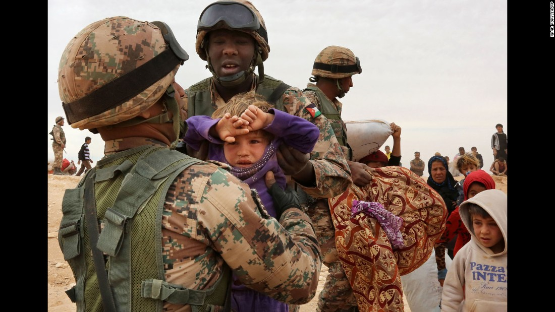 Jordanian soldiers help women and children seeking refuge from Syria on Wednesday, May 4.