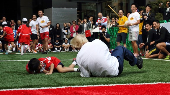 """London Mayor Boris Johnson knocks over 10-year-old Toki Sekiguchi during a touch rugby game in Tokyo on October 15, 2015. """"I accidentally flattened a 10-year-old on TV unfortunately,"""" Johnson said in a speech to British and American businessmen. """"But he bounced back, he put it behind him. The smile returned rapidly to his face."""""""