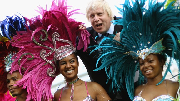 Johnson poses with members of a Carnival band in London on August 24, 2011.