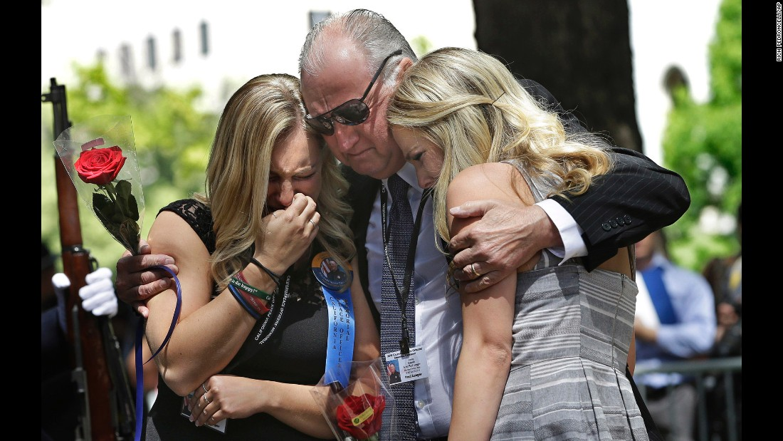 Paul Lunger comforts his granddaughters Ashton, left, and Sara after they placed roses at the California Peace Officers' Memorial on Monday, May 2. Ashton and Sara are the daughters of Police Sgt. Scott Lunger, who was fatally shot during a traffic stop in July. His name was among those added to the memorial in Sacramento.