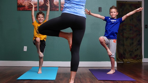 Santas, Luke and Nolan stand in happy hopping tree pose, which improves balance, coordination and movement control.