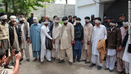 "Pakistani police escort blindfolded suspects accused of killing and setting fire to a woman as they appear at a court in Abbottabad on May 5, 2016.   A Pakistani woman was drugged, strangled and then her body set ablaze because she helped her friend elope, police said May 5, announcing the arrest of 14 people in a twist on the grim practice of ""honour killings"". / AFP PHOTO / SHAKEEL AHMEDSHAKEEL AHMED/AFP/Getty Images"