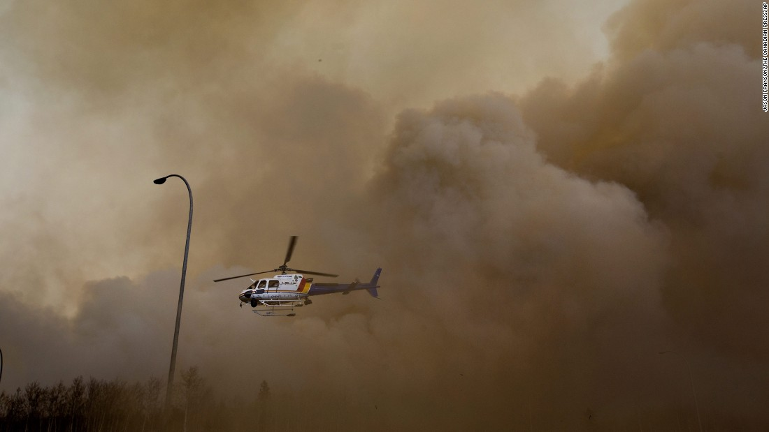 A police helicopter lifts off through dust and smoke on May 6.