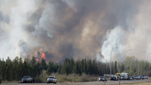 Wild fires burn south of Fort McMurray, Alberta, seen from highway 63 Friday, May 6, 2016. Displaced residents at oil field camps north of Fort McMurray, Alberta, got a sobering drive-by view of their burned out city Friday in a convoy that moved evacuees south amid a massive wildfire that officials fear could double in size by the end of Saturday. As police and military oversaw the procession of hundreds of vehicles, a mass airlift of evacuees also resumed.  (Jonathan Hayward/The Canadian Press via AP) MANDATORY CREDIT