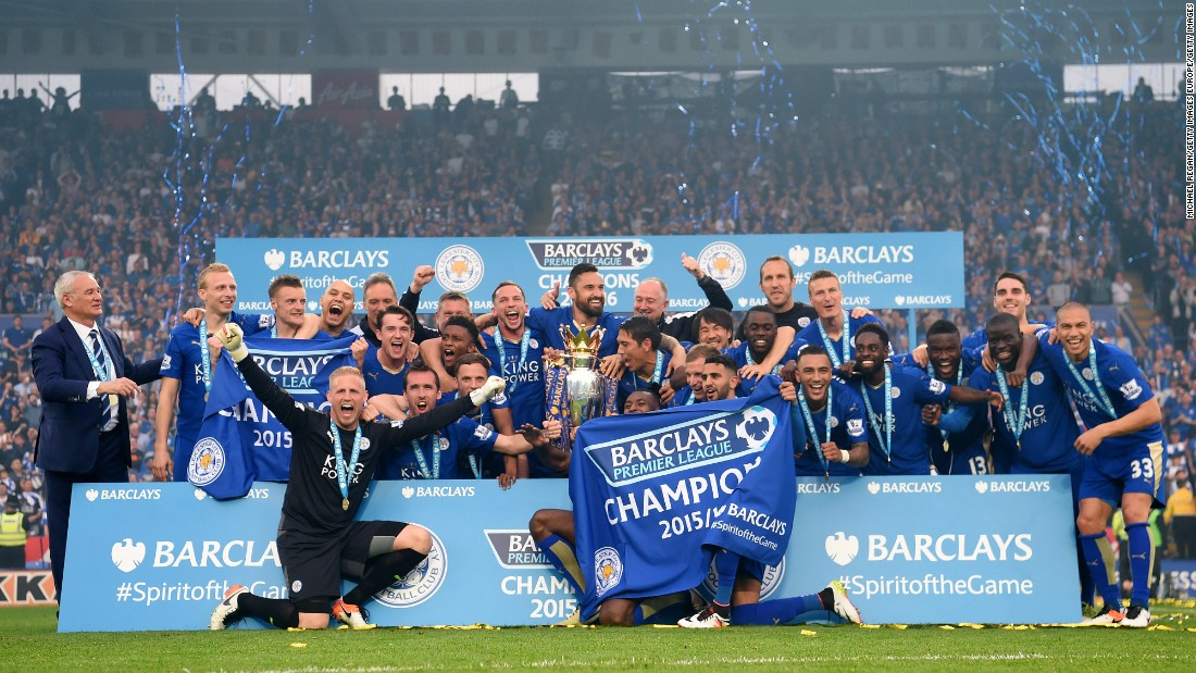 Leicester City players celebrate together with the Premier League trophy.